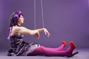 Fashion model stylized as marionette doll sitting on violet studio background