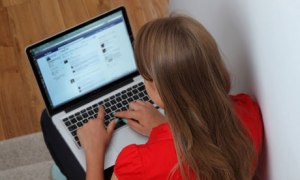 Young girl using laptop on Facebook page