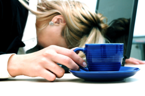 Tired woman are sleeping and holding cup. Laptop is situated on the table.